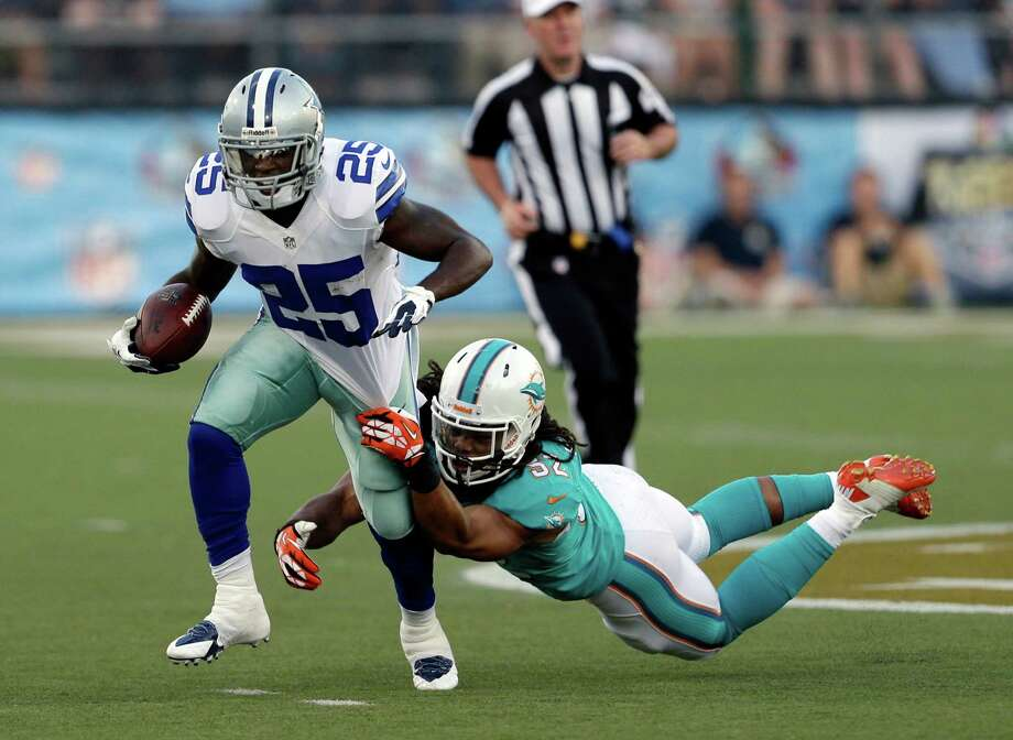 The Cowboys' Lance Dunbar picks up 11 yards by shedding Dolphins linebacker Philip Wheeler. Photo: Tony Dejak, STF / AP