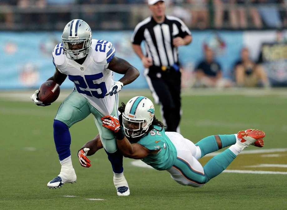 The Cowboys' Lance Dunbar picks up 11 yards by shedding Dolphins linebacker Philip Wheeler. Photo: Tony Dejak, STF / AP
