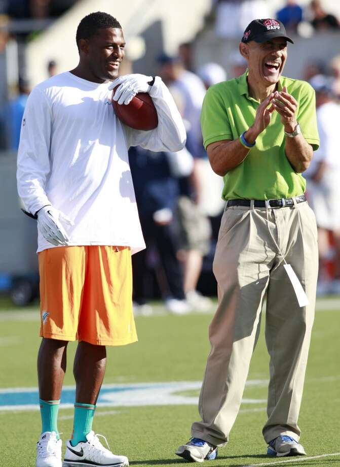 Miami Dolphins wide receiver Mike Wallace, left, talks with former NFL coach Tony Dungy before the Dolphins play the Dallas Cowboys at the Pro Football Hall of Fame exhibition football game Sunday, Aug. 4, 2013, in Canton, Ohio. (AP Photo/Scott R. Galvin) Photo: Scott R. Galvin, Associated Press