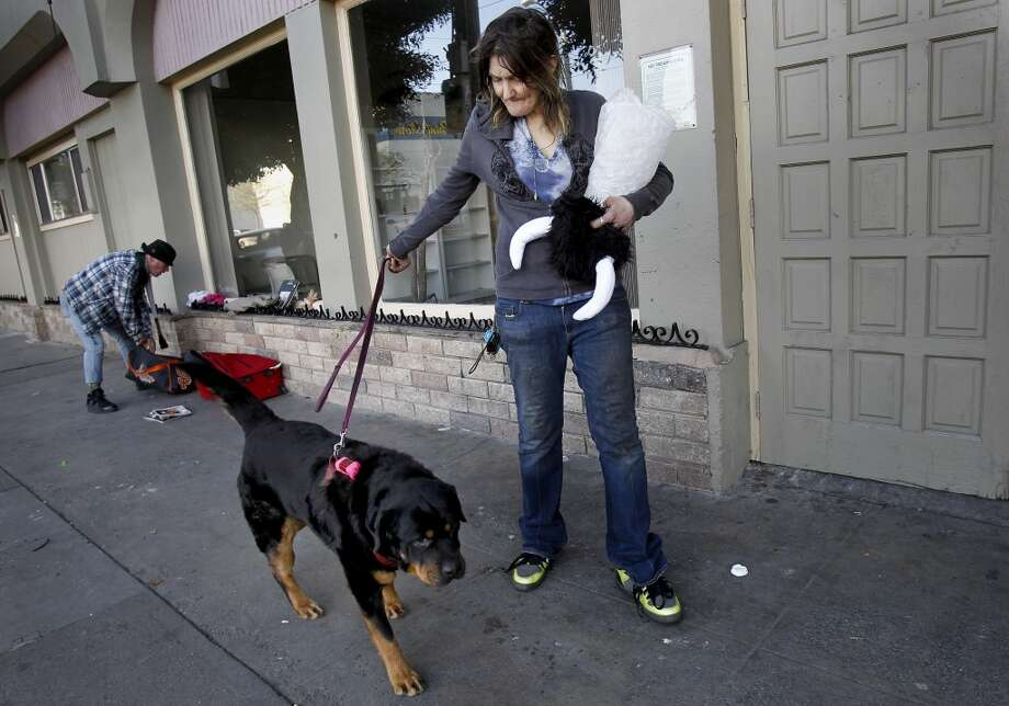 Brenda Clark walks her dog Bear past the Mission Hotel to return to her encampment nearby. Brenda Clark is fighting with the management of the Mission Hotel over her supportive housing room which she says is infested with cockroaches. The hotel is trying to evict the sometimes homeless woman and her dog named Bear. Photo: Brant Ward, The Chronicle