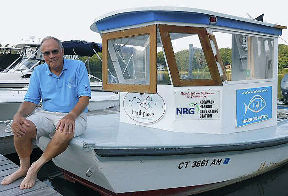 "Dick Harris, director of Earthplace's Harbor Watch program, sits on the prow of ""Annie,"" the group's research boat last year. Photo: File Photo / Westport News"