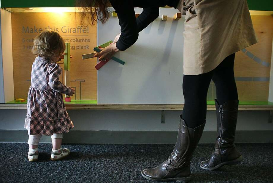 Charlotte Edwards, an 18-month-old from San Francisco, gets help from her mother as she builds with magnetic wooden blocks at the Tegu installation in the Creativity Museum in San Francisco. Photo: Liz Hafalia, The Chronicle