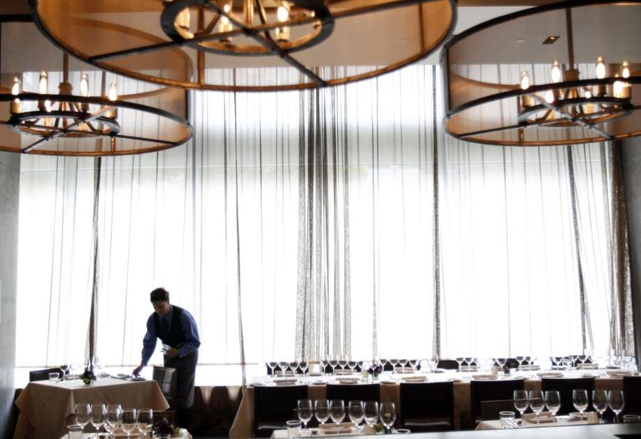 """A server prepares the tables for the """"Masters of Their Craft: Celebrating the Great Female Chefs and Sommeliers of San Francisco"""" fundraising dinner. Photo: Sarah Rice, Special To The Chronicle"""