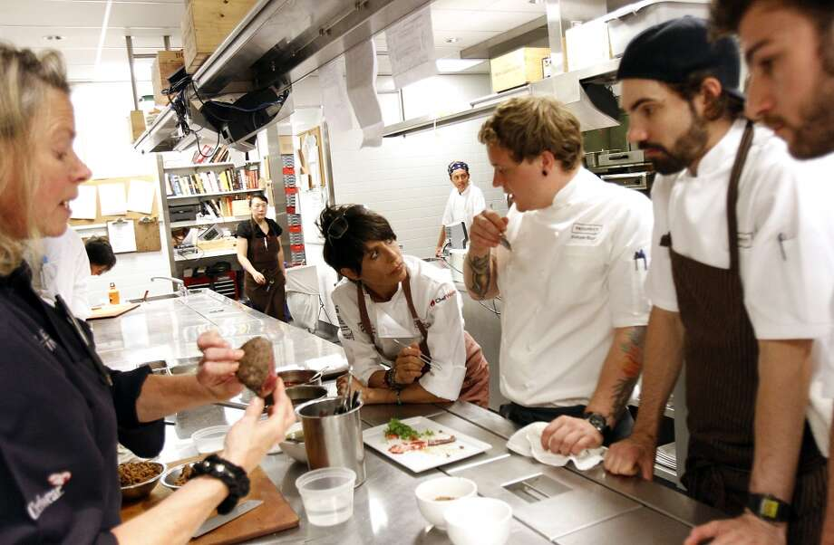 "Dominique Crenn, center, of Atelier Crenn, tries out a dish at the ""Masters of Their Craft: Celebrating the Great Female Chefs and Sommeliers of San Francisco"" fundraising dinner. Photo: Sarah Rice, Special To The Chronicle"