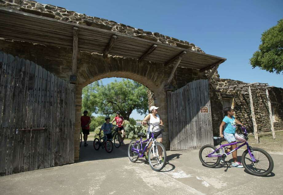 Cyclists arrive at Mission San Jose July 13 during a bicycle ride organized by Roll Models and the San Antonio Housing Authority. Roll Models is a program that helps kids and families bike to areas outside of their own neighborhoods. Photo: Darren Abate/For The Express-News