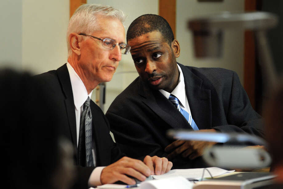 "Russell Peeler Jr., right, confers with his defense lawyer Robert Sullivan on the first day of his murder trial in Bridgeport Superior Court, in Bridgeport, Conn., Aug. 5th, 2013. Peeler is on trial for the 1998 shooting death of Rudolph Snead Jr., and has already been convicted and sentenced to death for ordering the murder of Karen Clarke and her eight-year-old son, Leroy ""B.J."" Brown Jr. in their Bridgeport, Conn. home in 1999. Photo: Ned Gerard / Connecticut Post"