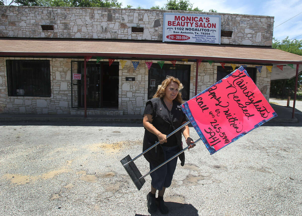Small business owner Monica Prater places a help wanted sign in front of her new business. Prater recently opened her new hair salon on Nogalitos Street with the help of a $170,000 Small Business Loan.