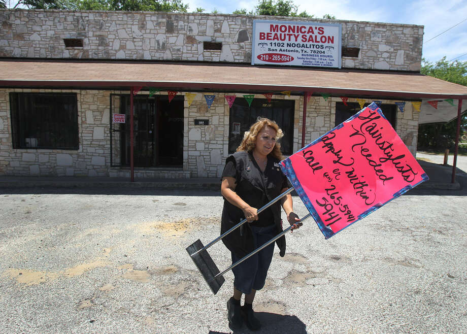 Small business owner Monica Prater places a help wanted sign in front of her new business. Prater recently opened her new hair salon on Nogalitos Street with the help of a $170,000 Small Business Loan. Photo: San Antonio Express-News File Photo