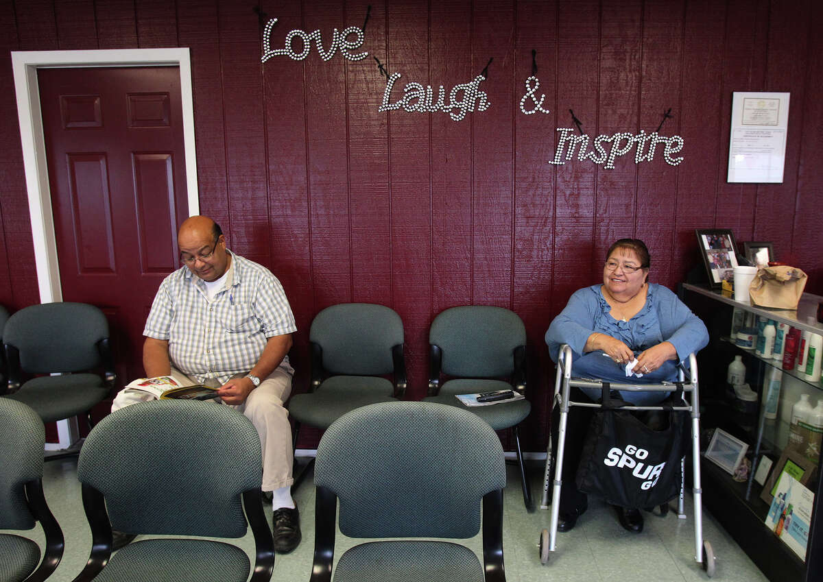 Customer David Escobedo (left) waits for a haircut Tursday July 16, 2013 at the recently opened Monica's Beauty Salon on Nogalitos street. The salon's owner, Monica Prater, was able to start the business with a 170,000 Small Business Administration-backed loan. Sitting on the right is Praters' mother, Oralia Gutierrez.