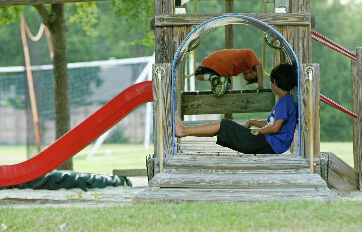 """Julian Hendrix and Kair Funaro play on the playground at Howard Early Childhood Center in the Alamo Heights ISD on Friday July 19, 2013. A research group called Salud America! from the UT Health Science Center did what the director called a """"comprehensive literature review"""" to conclude that 81 percent of Latino neighborhoods do not have a recreational facility, compared to 38 percent of white neighborhoods. The research shows access to playgrounds, gyms or sports fields make kids more likely to become physically active and maintain a healthy weight. In San Antonio, school playgrounds are often the only option but their policies vary widely."""
