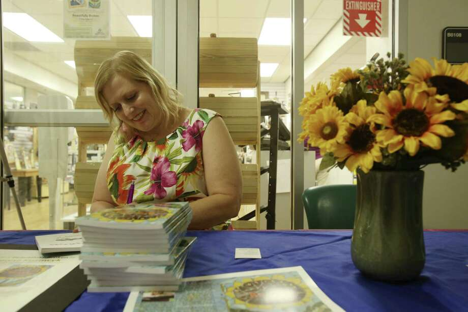 """Rebecca Kozowyk signs copies of her book, """"Beautifully Broken,"""" at University Hospital. """"Not one part of your life goes unchanged"""" after a traumatic brain injury, she says. Photo: Helen L. Montoya / San Antonio Express-News"""