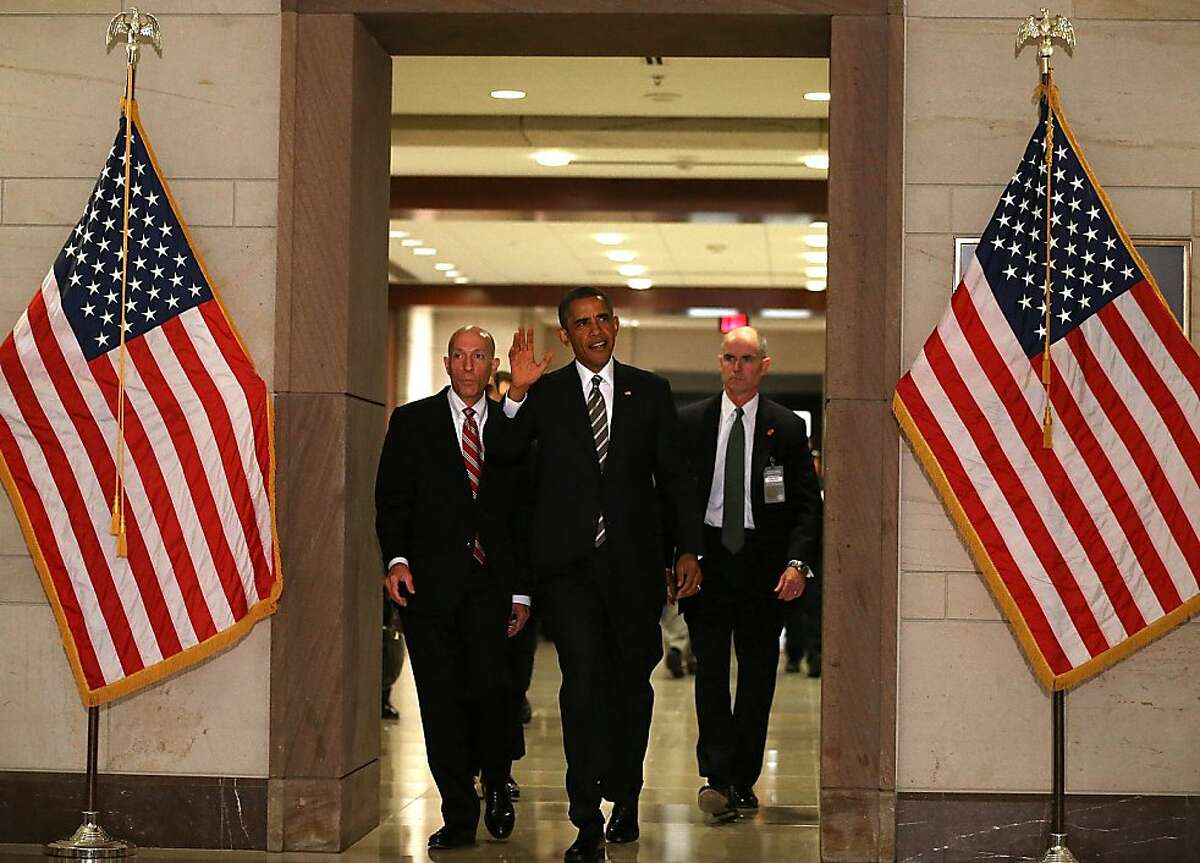 President Barack Obama (C) walks to a meeting with House Democrats on Capitol Hill, July 31, 2013 in Washington, DC. President Obama is expected to speak to the House Democrats about fiscal issues, job creation, and the Affordable Care Act. (Photo by Mark Wilson/Getty Images)