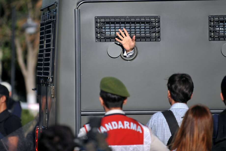 Hand signal:An Ergenekon prisoner waves to supporters from inside an armored police van at a