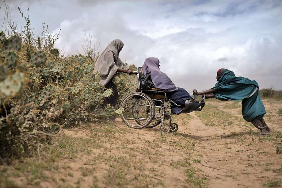 Off-roading in Afgoye:A Somalian woman in a wheelchair navigates through a hedge of cactus with a little help from her friends. The trio were headed to a food 