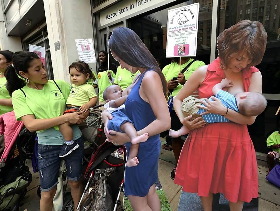 Moms rally around cardboard posters of breastfeeding women in the Washington Heights 