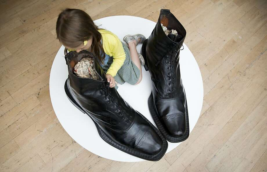 "As Ed Sullivan would say, we have really big shoe:Six-year-old Riva examines a pair of boots that would be roomy even for Shaquille O'Neal. The Victorian leather ""Ivy Brand"" Exhibition Balmoral boots are estimated to fetch between $15,000 and $18,500 when they go on sale Sept. 5 at Christie's in London. Photo: Matt Dunham, Associated Press"