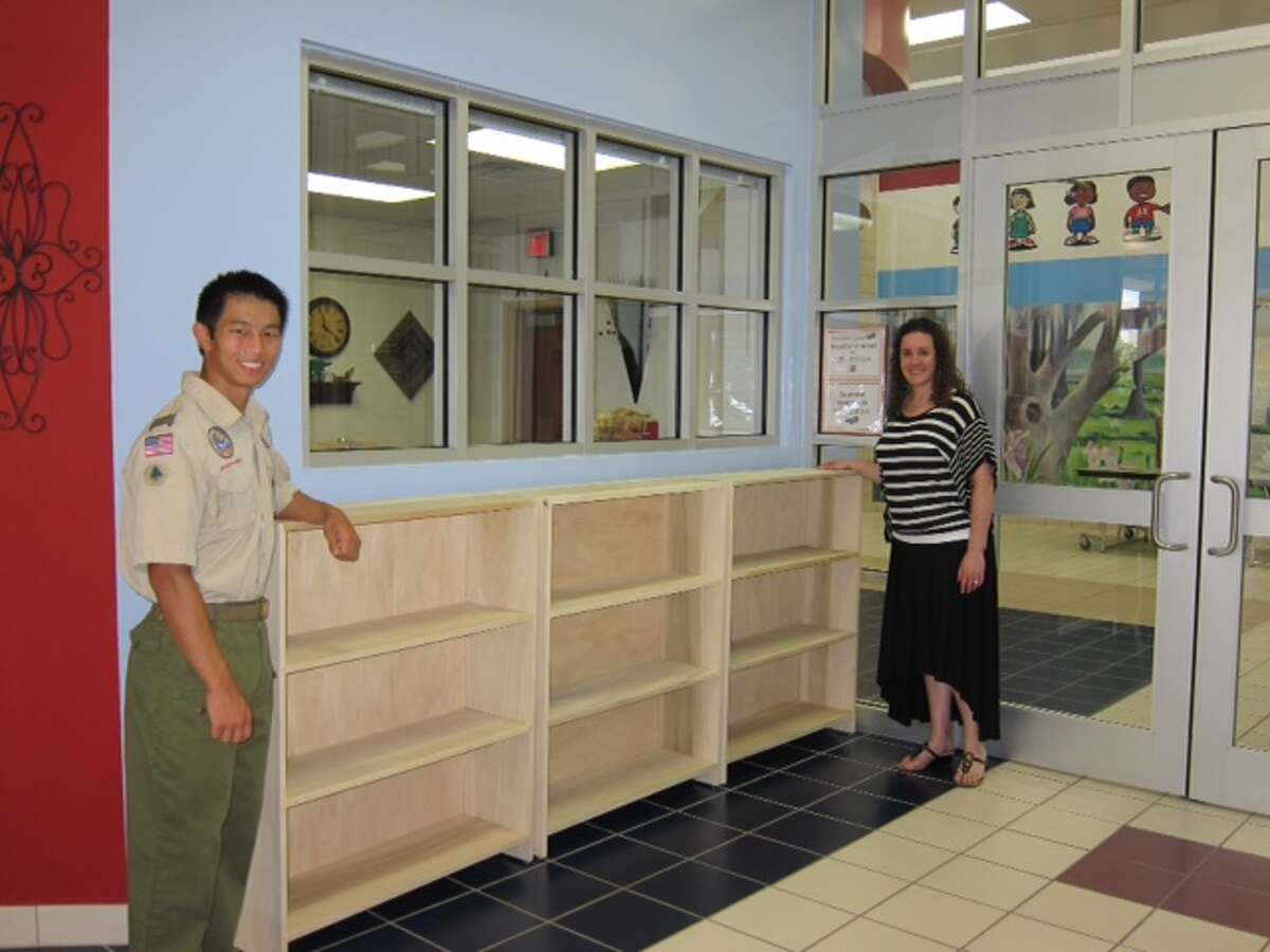 Michael Wang of Boy Scout Troop 1631 presents his Eagle project to Lori Craig, principal at Armstrong Elementary School.