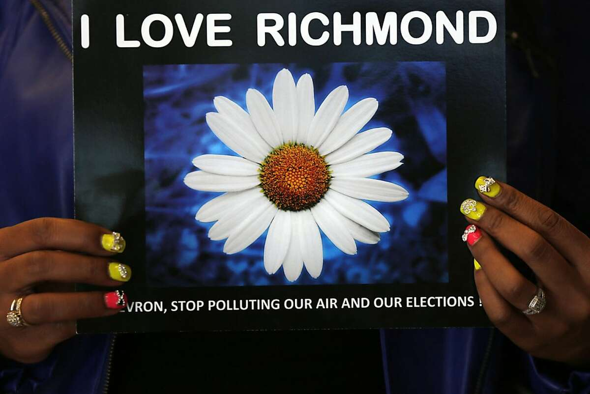 A woman holds a sign during a press conference about the City of Richmond's lawsuit against Chevron after a fire broke out in their refinery last year in Richmond, Calif. on August 2, 2013.