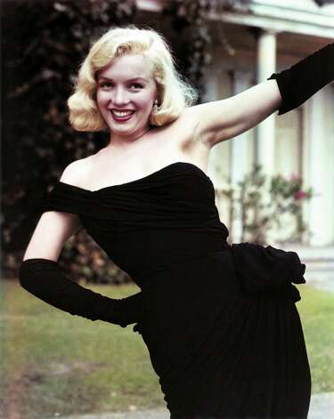 In 1950, Marilyn Monroe wears a black crepe cocktail dress by Ceil Chapman.