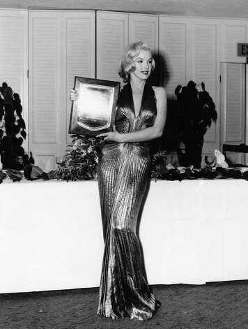 "In this March 1953 publicity photo provided by Running Press, Marilyn Monroe receives an award from Photoplay magazine at the Beverly Hills Hotel, in Beverly Hills, Calif. She is named ""Fastest Rising Star of 1952,"" and her choice of attire overshadows the event. The entire gown was made from ""one complete circle of fabric.""  Photo: Associated Press / Courtesy Running Press"