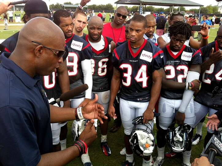 Hall of Fame defensive back Deion Sanders, left, talks to the Texans defensive backs after practice