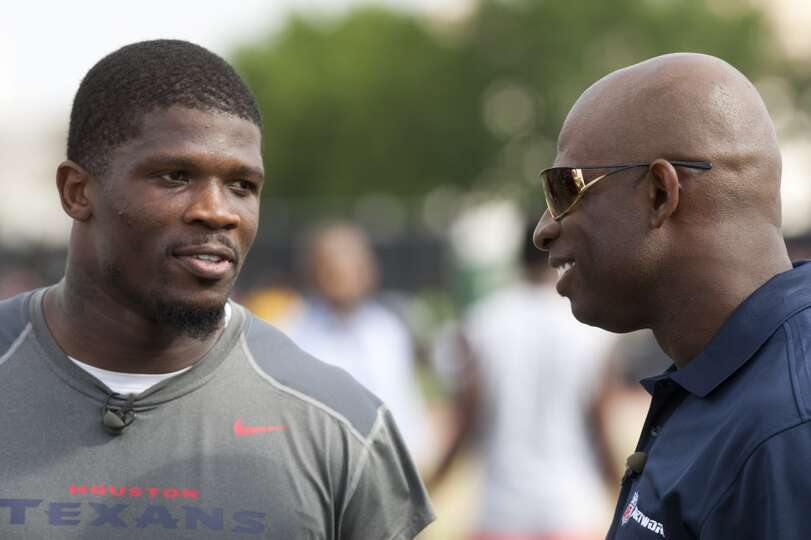 Wide receiver Andre Johnson, left, talks to Hall of Fame defensive back Deion Sanders at the end of