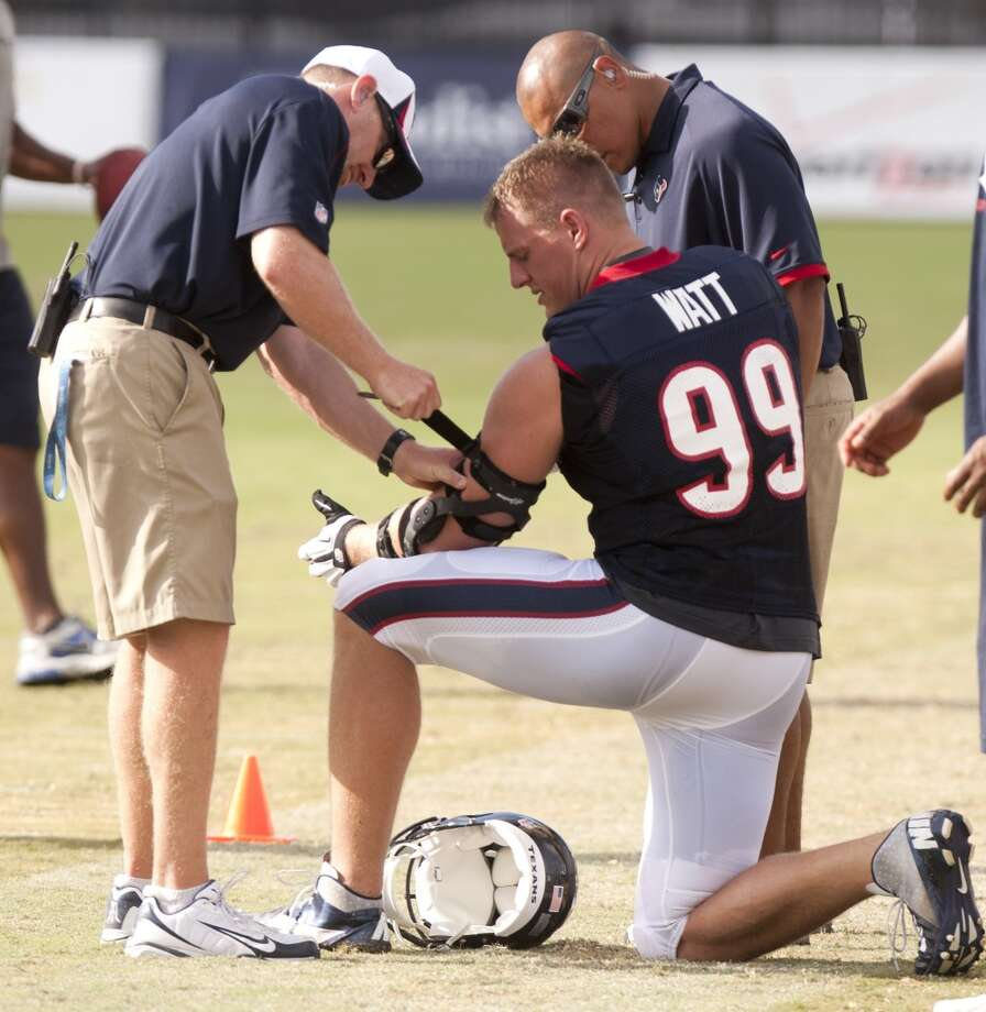 Trainer Geoff Kaplan, left, adjusts a stap on defensive end J.J. Watt's (99) elbow brace. Photo: Brett Coomer, Chronicle