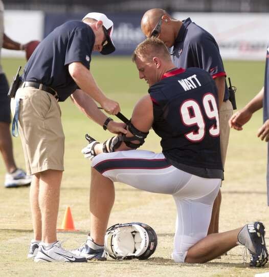 Trainer Geoff Kaplan, left, adjusts a stap on defensive end J.J. Watt's (99) elbow brace.