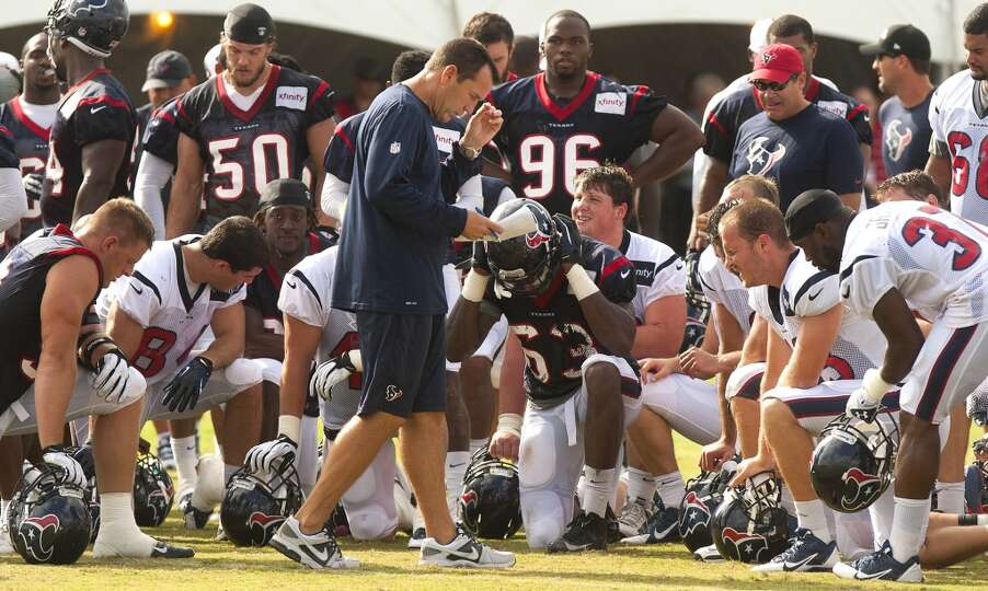Head coach Gary Kubiak gathers his players together at the end of practice.