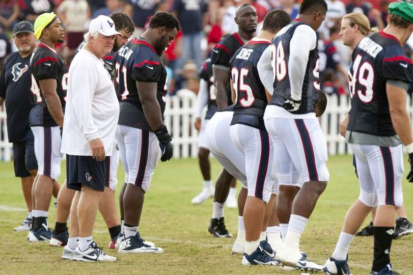 Defensive coordinator Wade Phillips walks to the line of scrimmage as the Texans defense walks throu