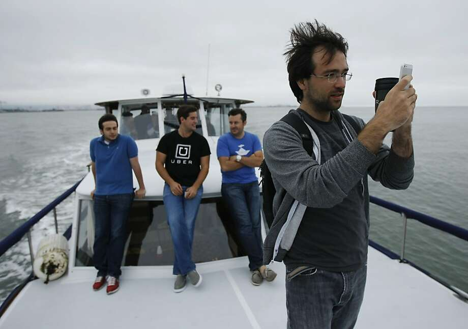 Victor Powell takes photos from the deck of the Peaceful Warrior on the morning commute to San Francisco. Photo: Rohan Smith, The Chronicle