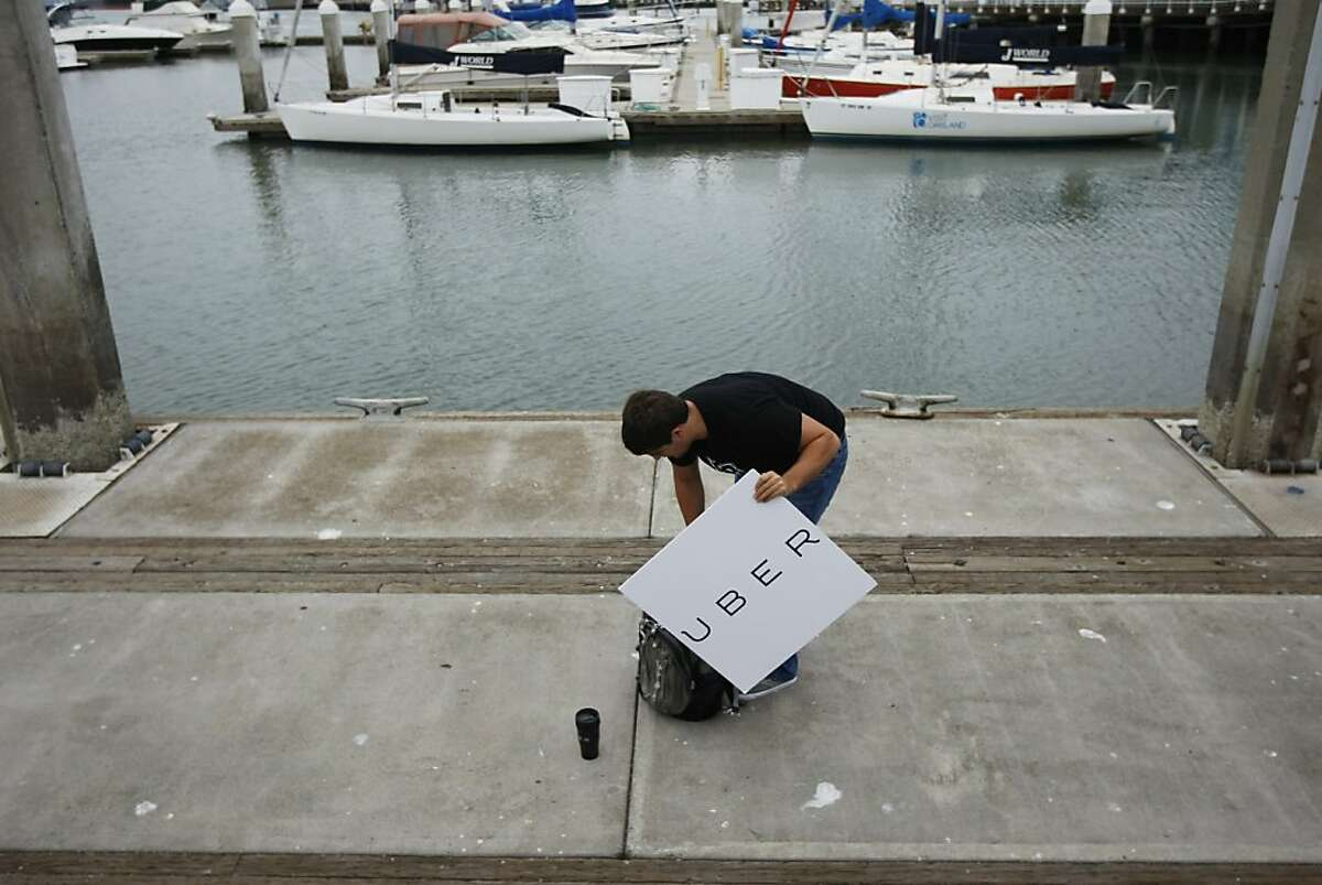 Uber operations manager, Rian Tolkin, picks up his stuff at the jetty at Jack London Square where Uber and Boatbound teamed up to provide a worker commute service to San Francisco in the event of a BART strike on Monday, August 05, 2013 from Oakland, Calif.