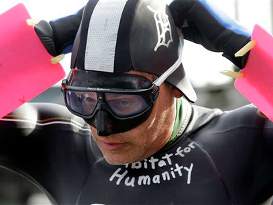 Jim Dreyer, a long-distance swimmer, adjusts his mask before taking off from the Clinton River Boat Club in Clay Township, Mich., Monday, Aug. 5, 2013 to swim 22 miles across Lake St. Clair while hauling dinghies filled with 2,000 pounds of bricks. Dreyer has made direct crossings of each of the five Great Lakes. The event is to raise funds and awareness for Habitat for Humanity. The swim is expected to take 30 hours and end Tuesday at Detroit's Belle Isle. (AP Photo/Carlos Osorio) Photo: Carlos Osorio, ASSOCIATED PRESS / AP2013