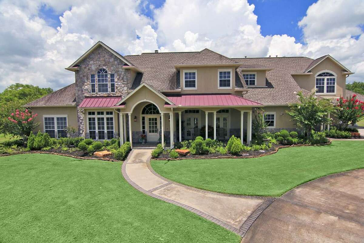 This Samson Custom Homes-constructed property has a circular driveway and port cochere.