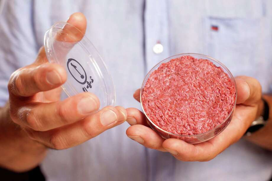 A Cultured Beef Burger made from beef grown in a lab from cattle stem cells is held by the man who developed it, Professor Mark Post of the Netherlands. Photo: David Parry, SUB / PA