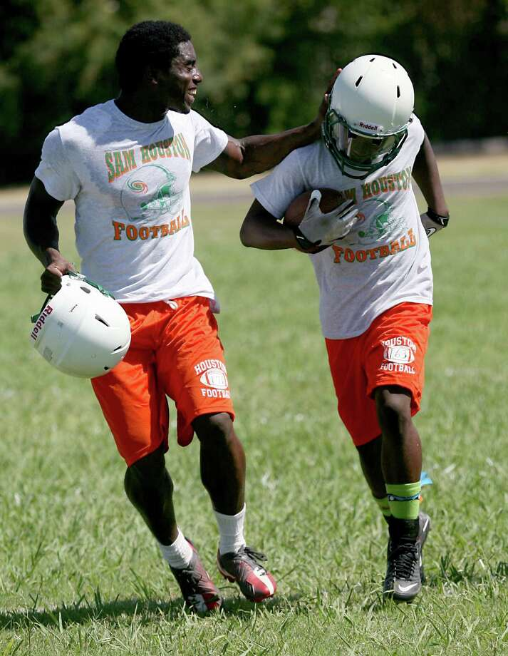 Sam Houston High School's Travon Vaughns (right) completes a play Monday, Aug. 5, 2013 with encouragement from teammate Tomaria Stringfellow during  football practice. It was the first day of practice for the team and lasted three hours. Photo: Cynthia Esparza, For The Express-News / San Antonio Express-News