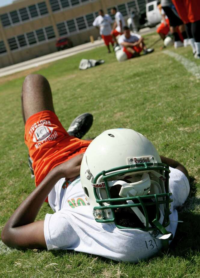 Sam Houston High School's Lionell Carter rests and tries to block the sun Monday, Aug. 5, 2013 during the 20 minute break the football team had on the first day of practice. Practiced lasted for three hours with many water breaks. Photo: Cynthia Esparza, For San Antonio Express-News / For San Antonio Express-News