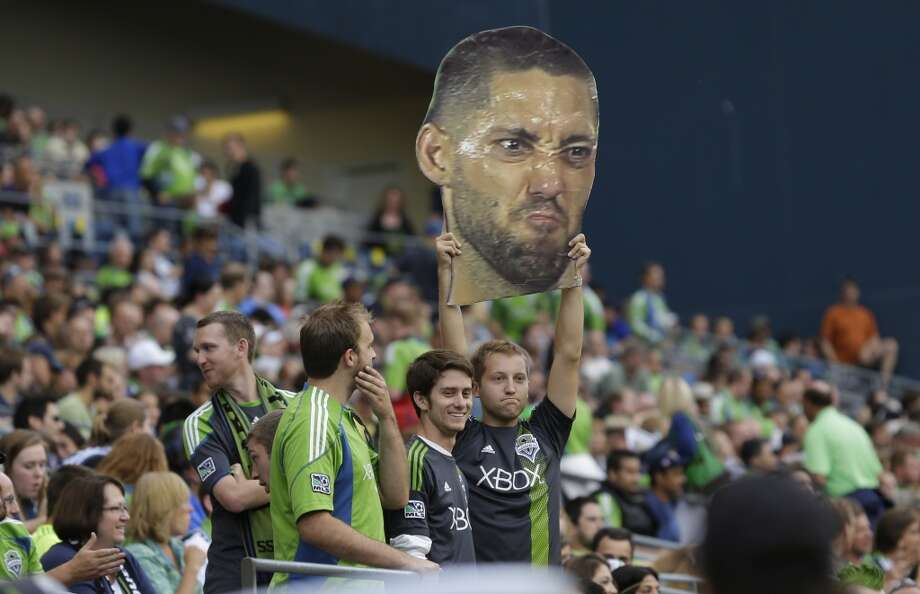 A fan holds a giant photo of Clint Dempsey on Saturday during a match between the Sounders and FC Dallas in Seattle. Dempsey, who previously played for Tottenham Hotspur in the English Premier League, was introduced as the newest member of the Sounders. Photo: Ted S. Warren, Associated Press