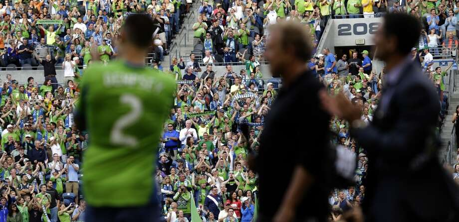 Fans cheer as Clint Dempsey, left, is introduced as the newest member of the Sounders on Saturday. Photo: Ted S. Warren, Associated Press