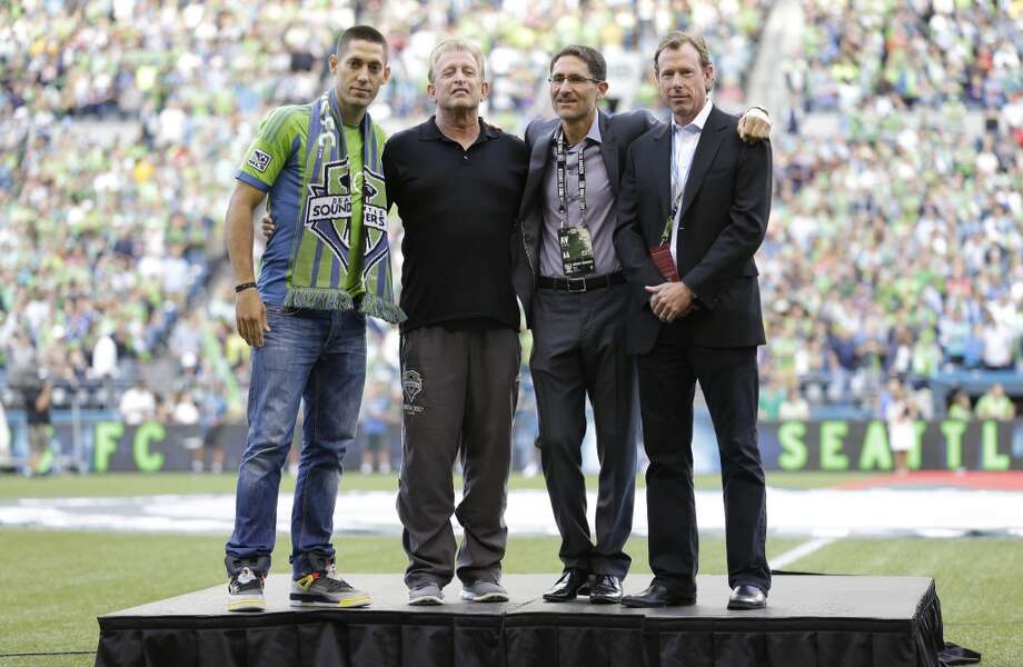 Clint Dempsey, left, poses for a photo with Sounders owner Joe Roth, second from left, Sounders general manager Adrian Hanauer, second from right, and Sounders president Peter McLoughlin, right, during a ceremony introducing Dempsey as the newest member of the Sounders on Saturday. Photo: Ted S. Warren, Associated Press