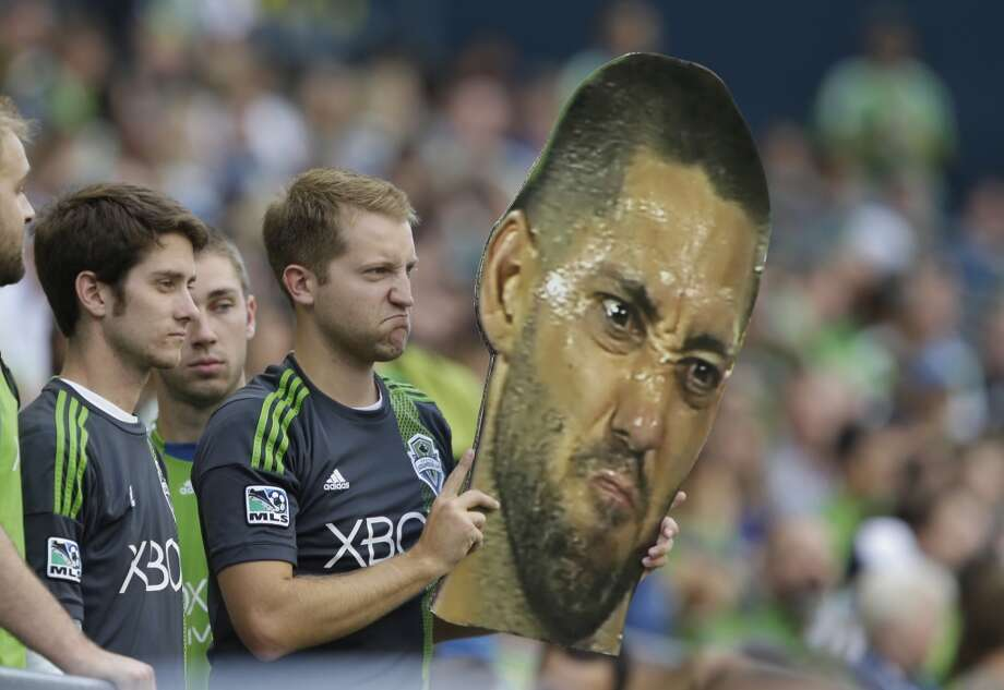 A fan holds a giant photo of Clint Dempsey on Saturday during a match between the Sounders and FC Dallas in Seattle. Photo: Ted S. Warren, Associated Press