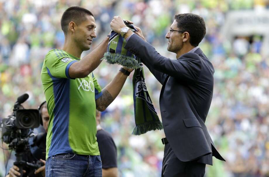 Clint Dempsey, left, is given a soccer scarf by Sounders general manager Adrian Hanauer after Dempsey was introduced as the newest member of the Sounders on Saturday. Sounders general manager Adrian Hanauer looks on at right. Photo: Ted S. Warren, Associated Press