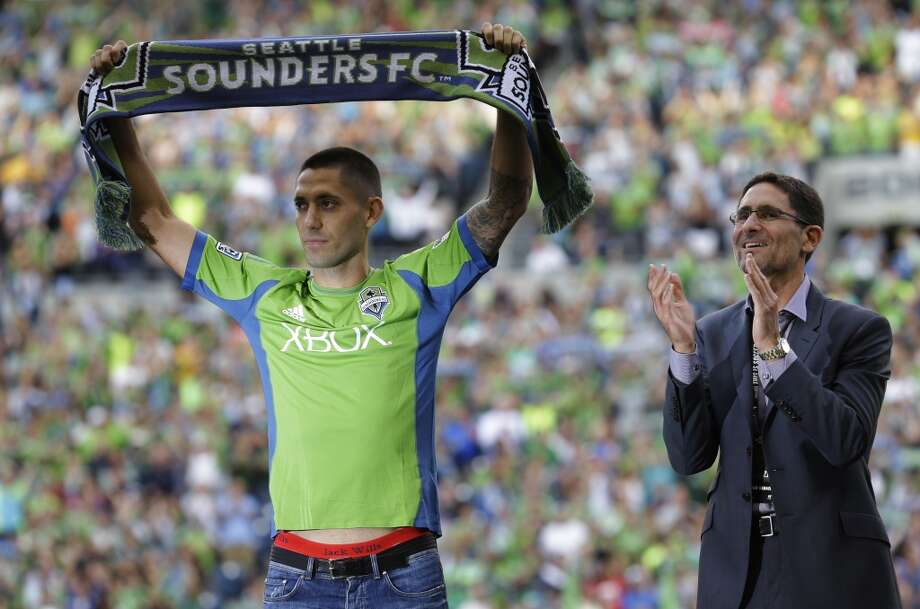 Clint Dempsey, left, is illuminated by a camera flash from the side as he holds up a scarf after he was introduced as the newest member of the Sounders on Saturday. Sounders general manager Adrian Hanauer looks on at right. Photo: Ted S. Warren, Associated Press