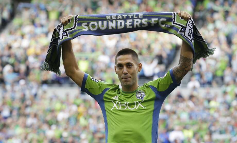 Clint Dempsey raises a Seattle Sounders scarf during a ceremony to introduce him as the newest member of the team Saturday. Photo: Ted S. Warren, ASSOCIATED PRESS