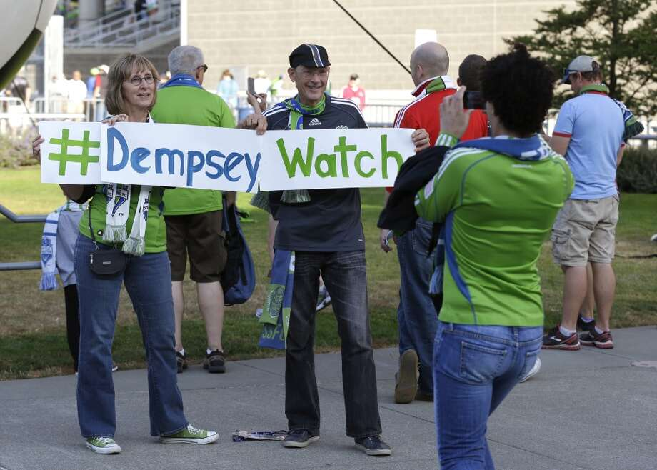 Seattle Sounders fans Larry McCann, right, and Nancy Cooper, left, both of Seattle, display a sign that has the Twitter hashtag #DempseyWatch outside CenturyLink Field before a MLS soccer match between the Sounders and FC Dallas. Clint Dempsey who previously played for Tottenham Hotspur in the English Premier League, had been linked by reports to joining the Seattle Sounders. Photo: Ted S. Warren, Associated Press