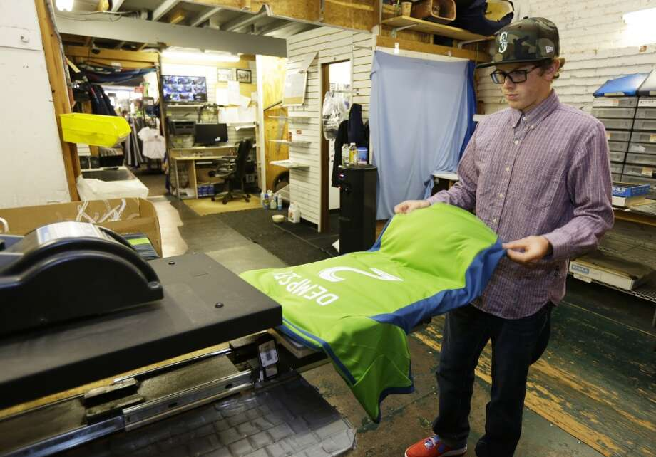 Josh Youngchild makes a Clint Dempsey No. 2 Sounders jersey Saturday at On the Field, a store that sells Seattle sports gear. Photo: Ted S. Warren, Associated Press