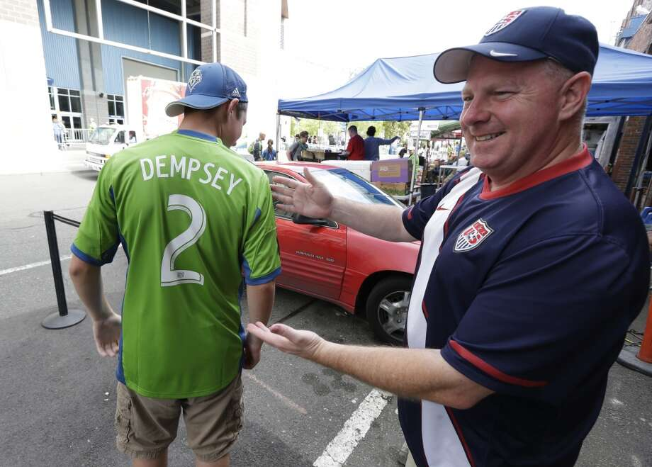 Evan Sacker, 14, left, of Vancouver, Wash., shows off his newly purchased Clint Dempsey No. 2 Sounders jersey Saturday outside CenturyLink Field in Seattle, as his father, Jeff Sacker, looks on at right. Photo: Ted S. Warren, Associated Press