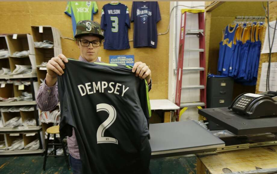 Josh Youngchild makes a Clint Dempsey No. 2 Sounders jersey Saturday at On the Field, a store that sells Seattle sports team gear. Photo: Ted S. Warren, Associated Press