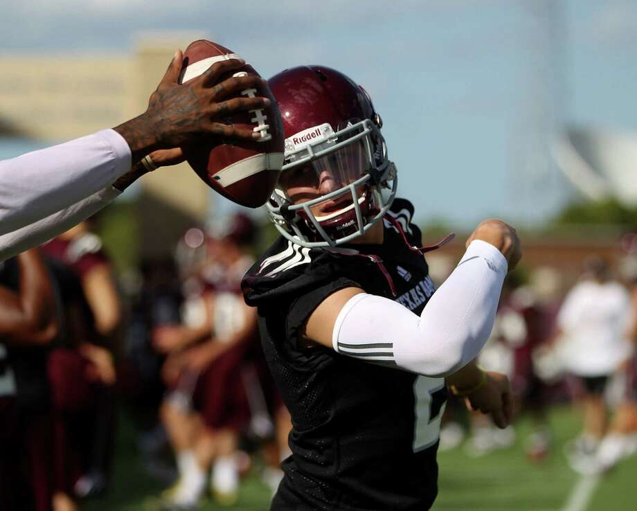 Texas A&M quarterback Johnny Manziel (2) is handed the ball by a teammate during Texas A&M's first workout, Monday, Aug. 5, 2013, in College Station. Photo: Karen Warren, Houston Chronicle / © 2013 Houston Chronicle