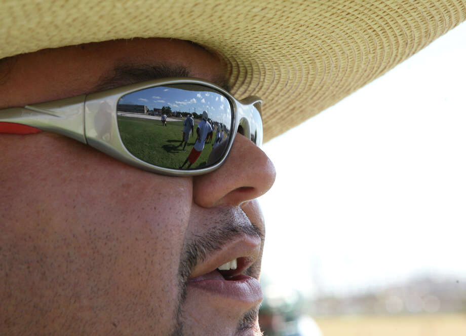 Sam Houston High School line coach Phillip Jimenez watches Monday, Aug. 5, 2013 as players do offensive and defensive drills on the first day of practices. Photo: Cynthia Esparza, For San Antonio Express-News / For San Antonio Express-News